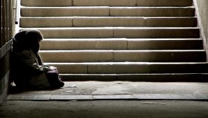 Homeless person at bottom of stairs